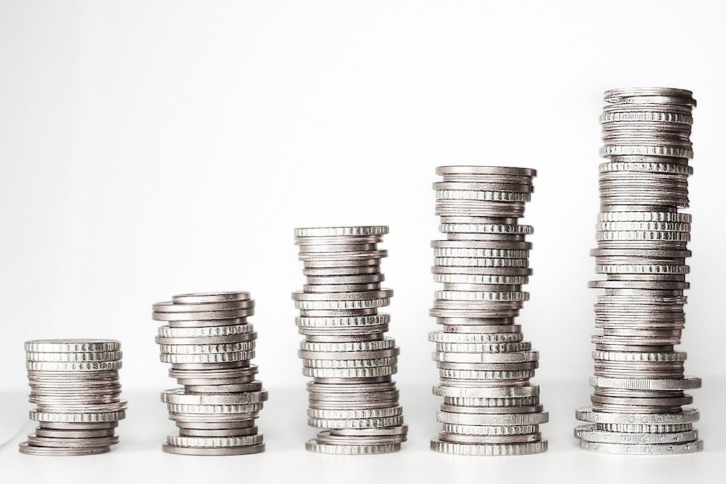 5 stacks of silver coins with a white background