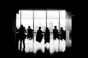 Black and white picture of people sat in front of a window.