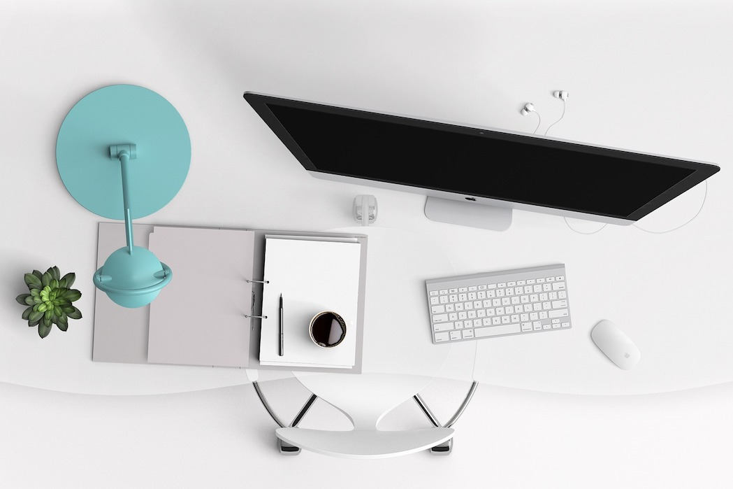 White desk with diary, computer and blue lamp